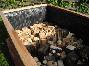 Altholz oder Scheitholz in den Hochbeetkasten einschlichten